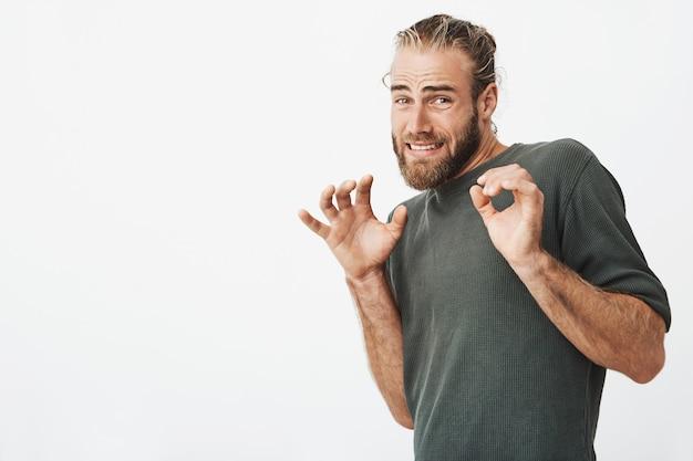 Knappe man met stijlvolle haren en baard schreeuwen met bang expressie