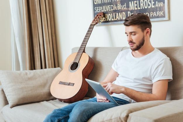 Knappe man met tabletcomputer op de bank thuis