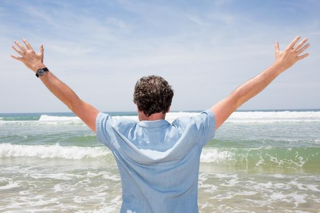 Knappe man met uitzicht op de oceaan met zijn armen in de lucht