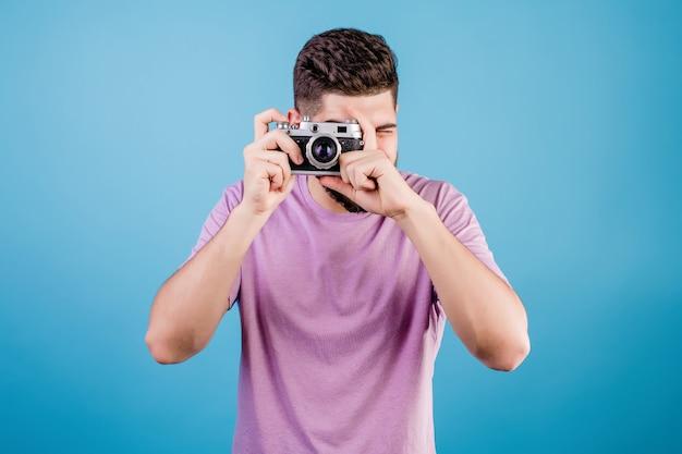 Knappe man met vintage fotocamera geïsoleerd op blauw