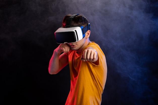 Knappe man met virtual reality headset op donkere ondergrond