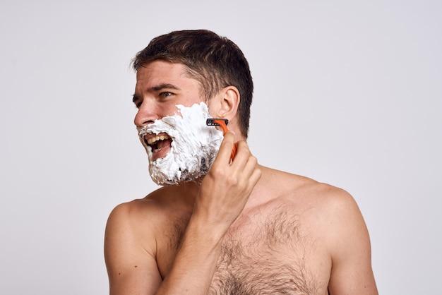 Knappe man met wit scheerschuim op zijn gezicht en schone huid met scheermesje dat blote schouders verzorgt.