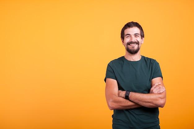 Knappe man met zijn armen gekruist glimlachen naar de camera geïsoleerd op gele achtergrond. portret van aantrekkelijke bebaarde zelfverzekerde persoon in studiofoto
