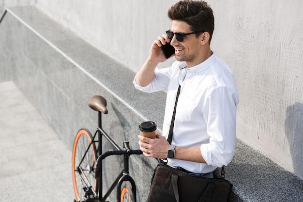 Knappe man met zonnebril, afhaalkoffie drinken en praten over de mobiele telefoon terwijl hij met de fiets langs de muur buiten staat