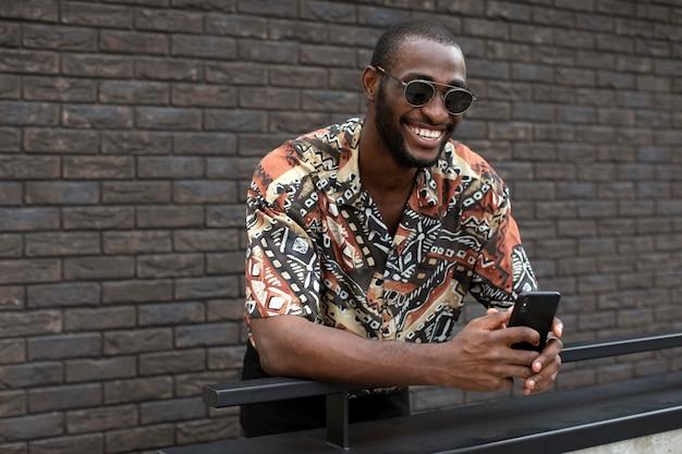 Knappe man met zonnebril met behulp van moderne smartphone buitenshuis