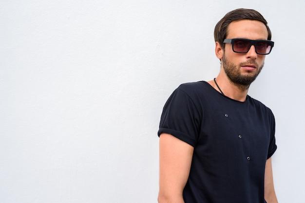 Knappe man met zwarte shirt en zonnebril tegen witte achtergrondkleur
