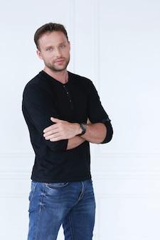 Knappe man met zwarte t-shirt en spijkerbroek poseren