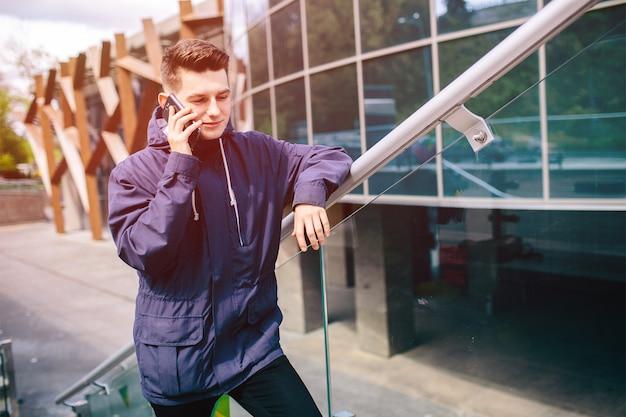 Knappe man mobiele telefoon buiten stad straat, jonge aantrekkelijke student casual blauw shirt praten