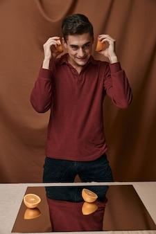 Knappe man modieuze kapsel spiegel op tafel sinaasappelen in handen. hoge kwaliteit foto