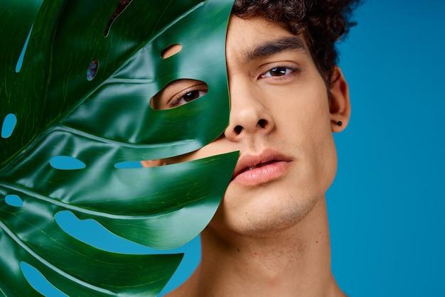 Knappe man naakte schouders groen blad heldere huid blauw