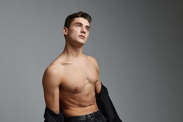 Knappe man naakte torso zwart shirt schattigheid poseren model.