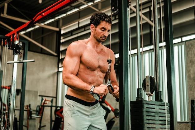 Knappe man oefenen in de sportschool body-building met gespierde sterke lichaam