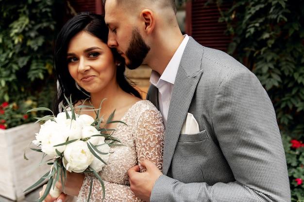 Knappe man of afro-amerikaanse bruidegom knuffelen mooi meisje of schattige bruid met mooie blonde haren in witte sexy trouwjurk buitenshuis op de achtergrond wazig stadsstraat
