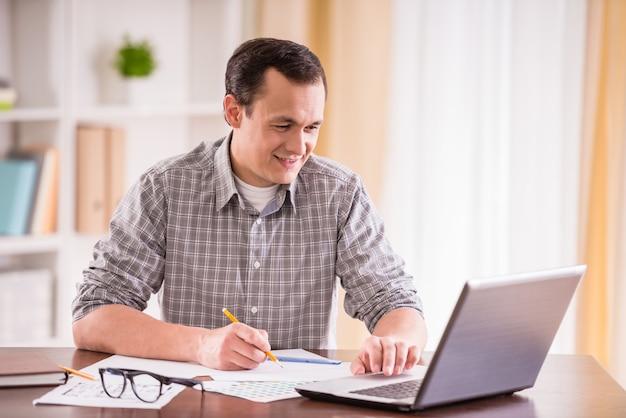 Knappe man om thuis te zitten aan tafel en laptop te gebruiken.