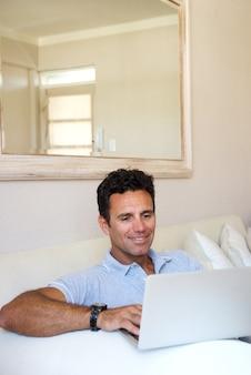 Knappe man om thuis te zitten met laptop
