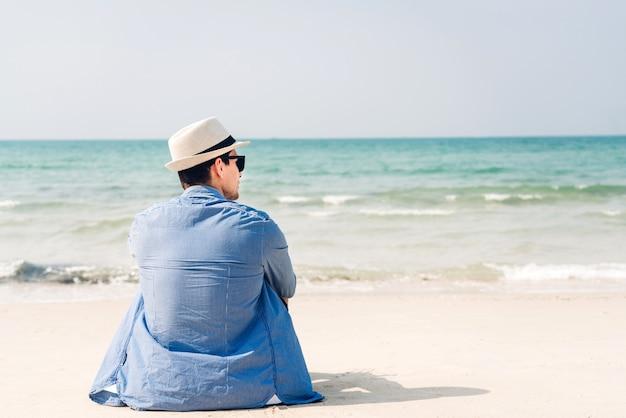 Knappe man ontspannen in zonnebril en stro hoed zittend op het tropische strand en op zoek naar de zee. zomervakanties