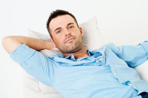 Knappe man ontspannen met de hand achter het hoofd