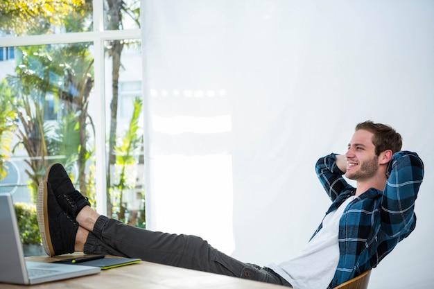 Knappe man ontspannen op zijn bureaustoel in een heldere kantoor