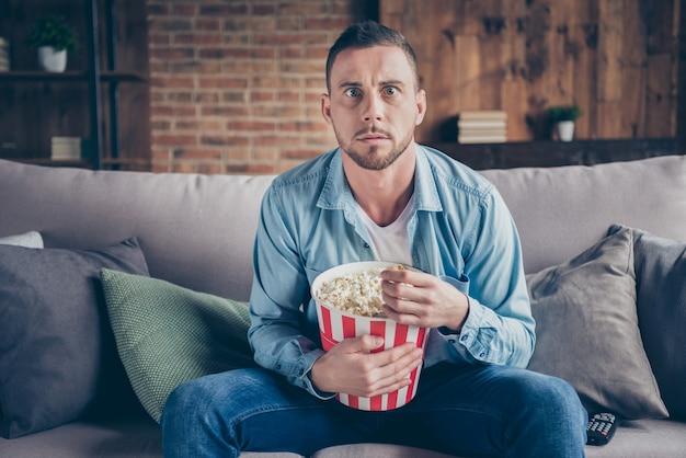 Knappe man ontspannen thuis blijven kijken naar televisie horrorfilm eten popcorn