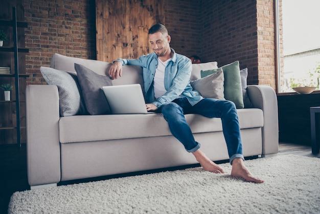 Knappe man op blote voeten ontspannen zitten comfortabele bank bladeren notebook