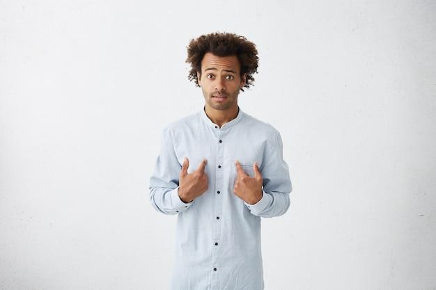 Knappe man op camera wijzend op zichzelf met handen wordt verrast