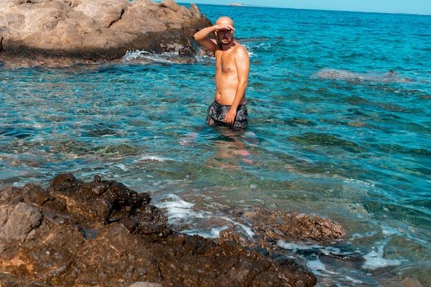 Knappe man op de rotsachtige kust