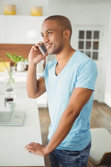 Knappe man op een telefoongesprek in de keuken