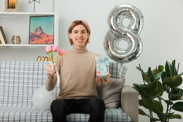 Knappe man op gelukkige vrouwendag met bloemen met cadeau zittend op de bank in de woonkamer