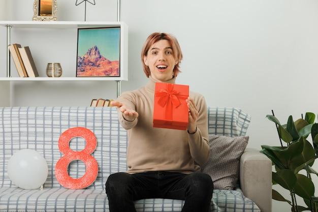 Knappe man op gelukkige vrouwendag met cadeau zittend op de bank in de woonkamer
