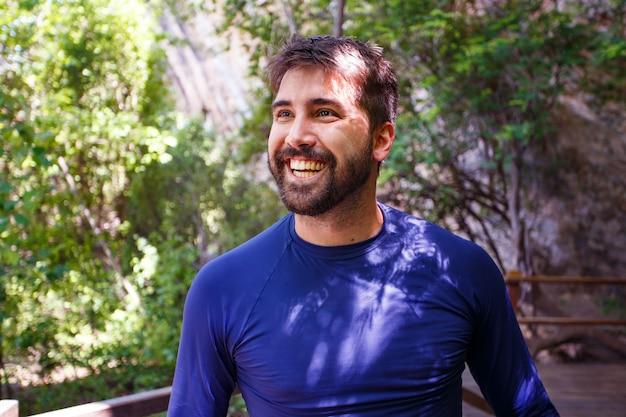 Knappe man op trail vakantie glimlachend camera kijken. man die lacht in het park.