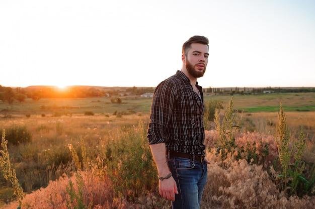 Knappe man op zonsondergang achtergrond. jonge man is op zoek bij zonsondergang. reiziger met rugzak