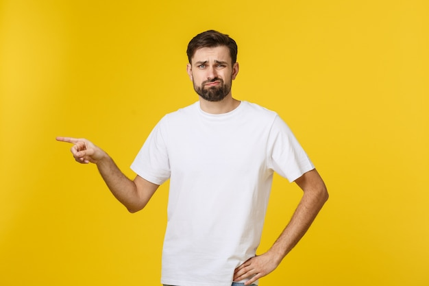 Knappe man over geïsoleerde gele muur gefrustreerd en naar voren wijzend