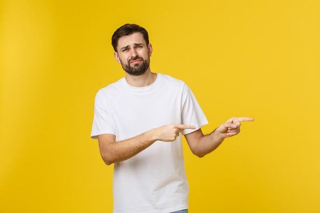 Knappe man over geïsoleerde gele muur gefrustreerd en wijzend op de voorkant.