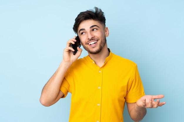 Knappe man over geïsoleerde muur houden van een gesprek met de mobiele telefoon met iemand