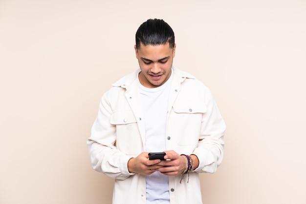 Knappe man over geïsoleerde muur verzenden van een bericht met de mobiel