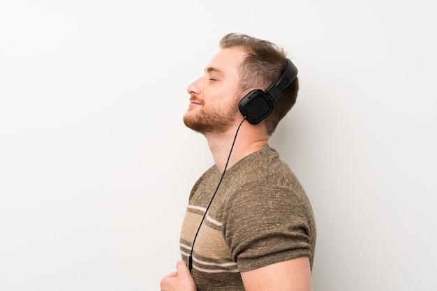 Knappe man over geïsoleerde witte muur luisteren naar muziek met een koptelefoon