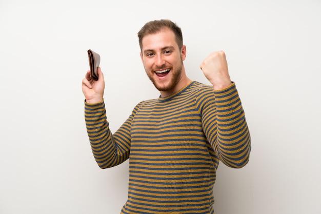 Knappe man over geïsoleerde witte muur met een portemonnee