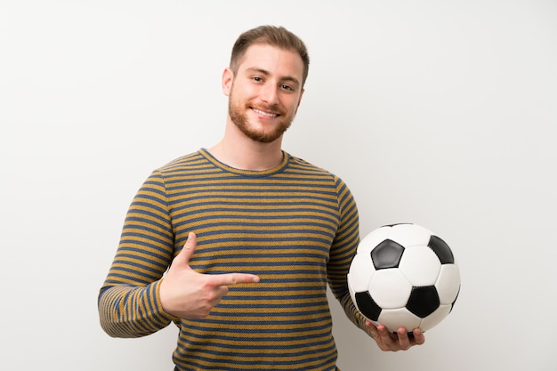 Knappe man over geïsoleerde witte muur met een voetbal