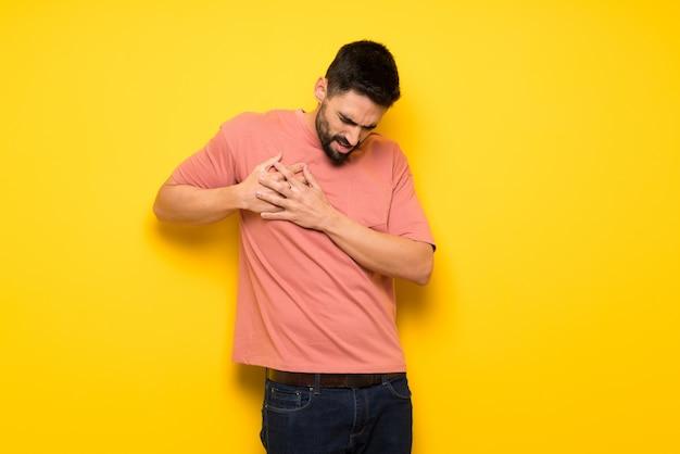 Knappe man over gele muur met een pijn in het hart