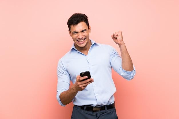 Knappe man over roze met telefoon in overwinningspositie