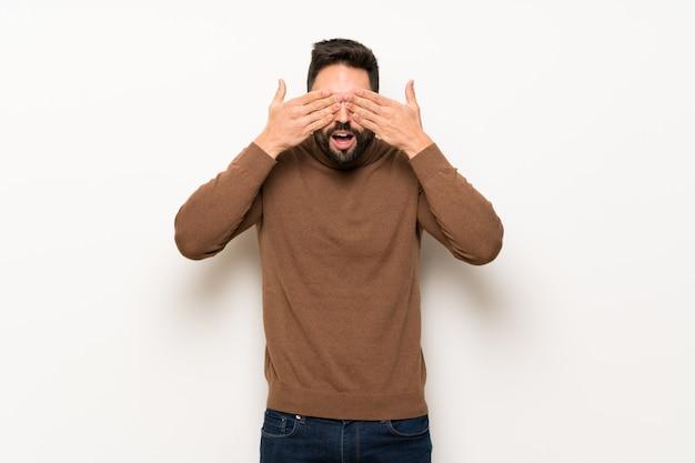 Knappe man over witte muur die ogen behandelt door handen. verrast om te zien wat er gaat gebeuren