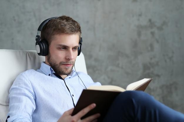 Knappe man podcast op koptelefoon luisteren