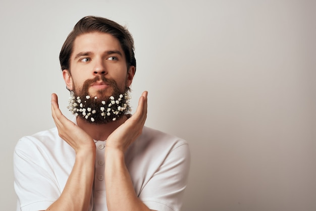 Knappe man poseren bloemen in een baard mode close-up