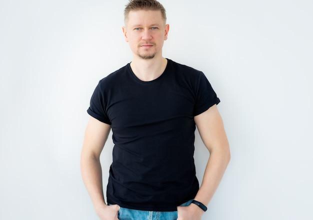 Knappe man poseren in zwarte lege tshirt