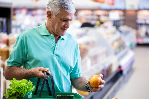 Knappe man poseren, kijken en fruit in de hand houden. bebaarde klant glimlachen. sectie met verse citrusvruchten op ruimte.
