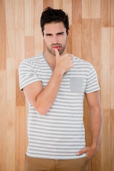Knappe man poseren voor houten achtergrond