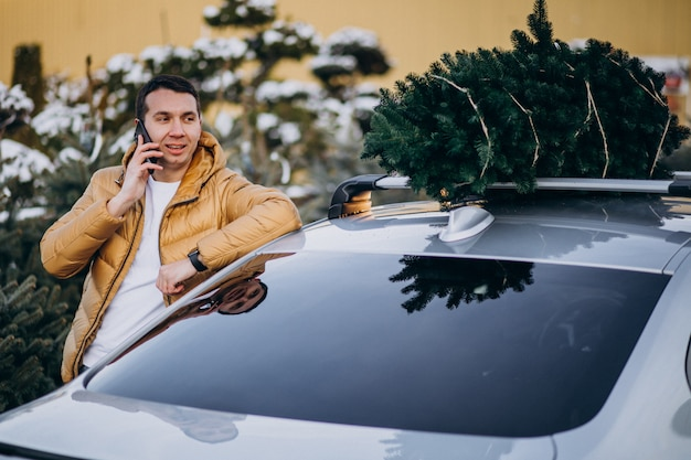 Knappe man praten over telefoon door de auto met kerstboom op de top