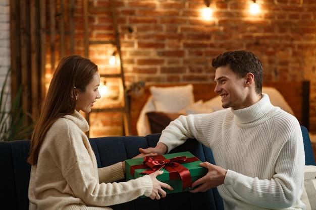 Knappe man presenteert een geschenk aan zijn mooie meisje en lacht