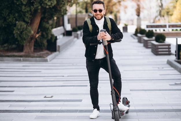 Knappe man rijden op scooter en koffie drinken uit thermos
