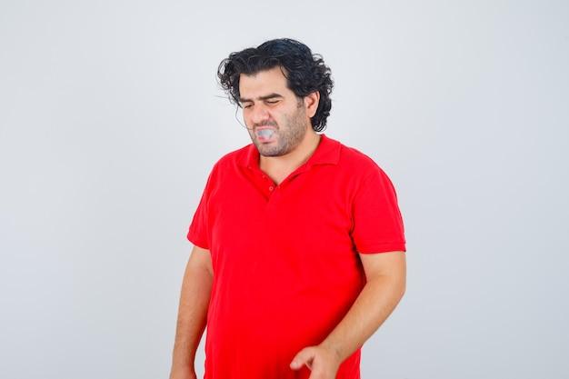 Knappe man roken sigaret, denken aan iets in rood t-shirt en peinzend, vooraanzicht op zoek.